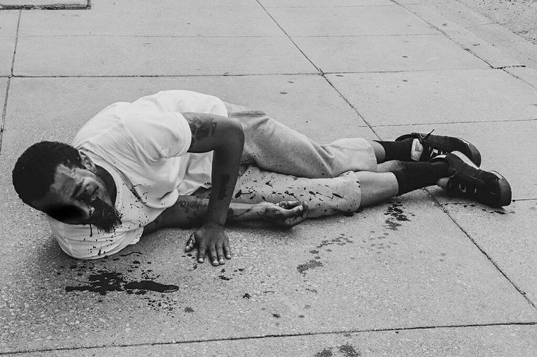 """Brandon Saenz lies on a sidewalk bleeding from his eye after a Dallas police officer shot him in the face with """"less-than-lethal"""" ammunition. - PHOTO PROVIDED BY ATTORNEY DARYL WASHINGTON"""