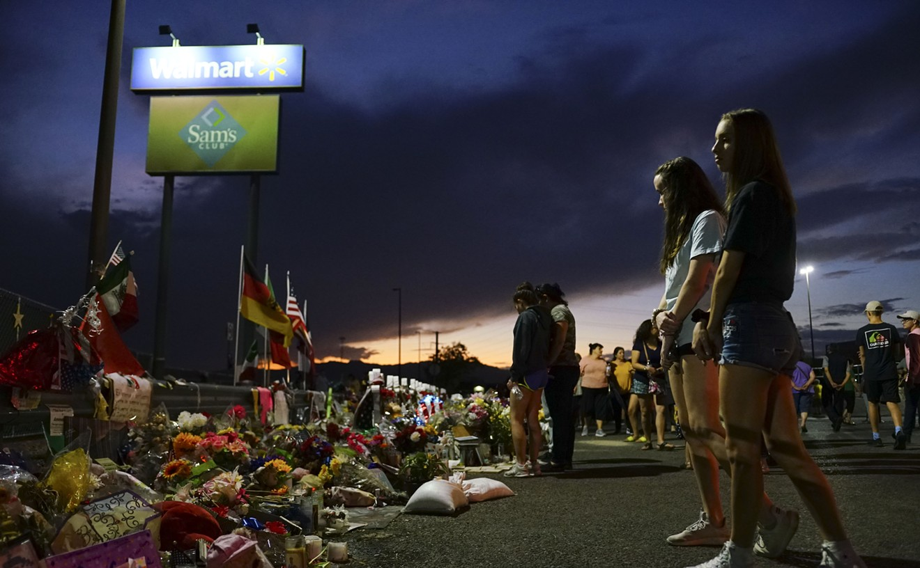 People gather at a makeshift memorial honoring victims of a mass shooting outside Walmart on Aug. 15, 2019, in El Paso.