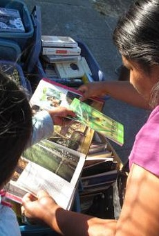 A neighborhood mom and her daughter sort through newly donated books.