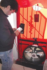 A Rising Sun Energy technician prepares to conduct a blower door test as part of a home energy audit.