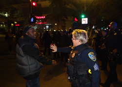 An officer orders a man crossing the intersection during a green pedestrian light to the sidewalk during Sunday's march against the nighttime protest ban. - DARWIN BONDGRAHAM