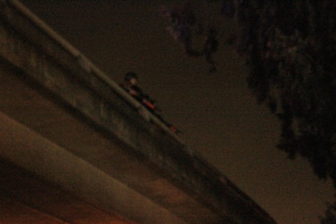 CHP officers, standing on a Highway 24 overpass, train their less-than-lethal weapons at protesters standing below on the street. - ALI WINSTON