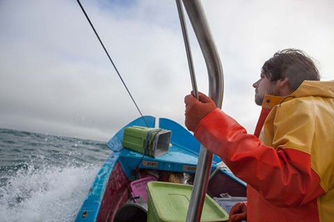 Alley says the advantage of his boat's size is increased speed and maneuverability, which allows him to fish in worse weather than larger boats. Here, his deckhand watches for buoys that mark the location of pots.