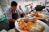 "CHRIS DUFFEY - Jalisco owner Antonio Vasquez prepares a ""mixed"" carnitas plate."