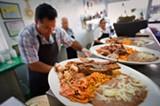 "CHRIS DUFFEY - Jalisco owner Antonio Vasquez prepares a ""mixed"" carnitas plate."