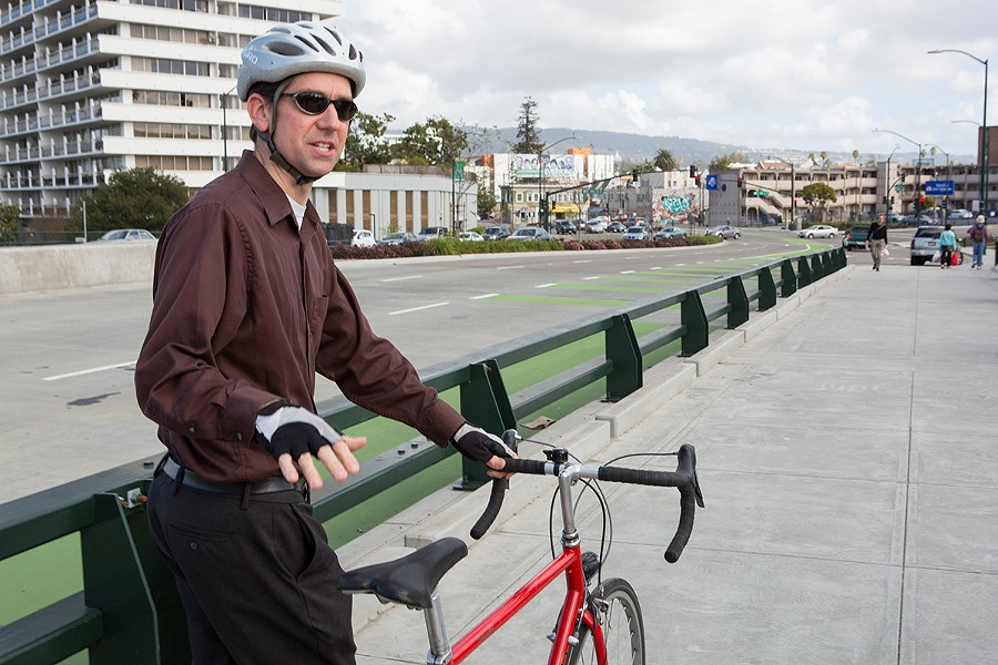 Jason Patton, bicycle and pedestrian program manager, standing by a green bike lane. - PHOTO BY BERT JOHNSON