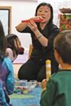 Kai-Yao To uses plastic linking blocks to teach a math lesson in Mandarin.