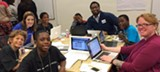 COURTESY OF THE LEVEL PLAYING FIELD INSTITUTE - Kalimah Priforce (background) and developers working with sixth-grade boys at a hackathon hosted by the Level Playing Field Institute.