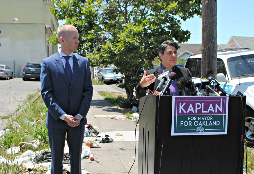 Kaplan stands in front of garbage while campaign manager Jason Overman looks on. - STEVEN TAVARES