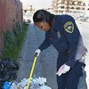Litter-enforcement officer Lerneda Lacy gathers evidence in      East Oakland.