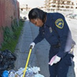 CHRIS DUFFEY - Litter-enforcement officer Lerneda Lacy gathers evidence in - East Oakland.