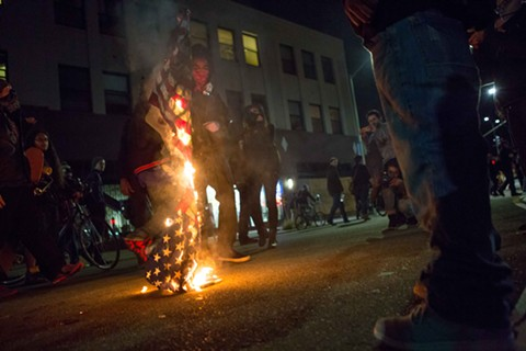 Toward the end of the march, protestors burn an American flag on Telegraph Avenue.