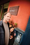 Restaurant owner Jack Stewart and his daughter Song-An in front of their hard-won gas meter.