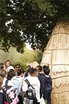 Ruth Orta shows schoolchildren a reconstructed Ohlone      house  in Coyote Hills Regional Park.