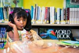 STEPHEN LOEWINSOHN - Sophia Sanchez enjoys a lunch at the César E. Chávez branch of the Oakland Public Library.