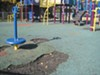The pocked playground surface at Linden Park in North Oakland poses a safety hazard for kids.