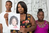 BERT JOHNSON - Tiffany Green (center) shows a photo of her daughter, Alana Williams, who was killed in a hit-and-run crash in 2009. Alana is survived by four siblings, including Joshua Williams Green (left) and A'zoria Williams Green.