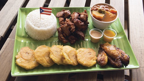 Combination meals are generously portioned, such as this chicharrones plate with tostones, beans, rice, and extra maduros. - PHOTO BY LANCE YAMAMOTO