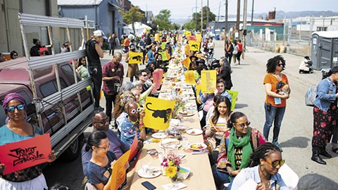 One long table ran down Magnolia Street for a two-hour meal, which featured performances, speeches, and questions about combatting gentrification in West Oakland. - PHOTO COURTESY OF SANA JAVERI KADRI