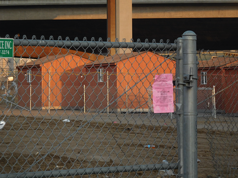 """A pink """"no camping"""" notice on a fence outside the Castro Street Tuff Shed camp shortly after it opened."""