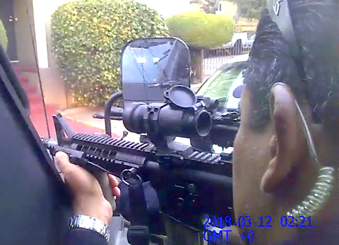 In a screenshot from a police body camera video, an OPD officer trains his rifle on Joshua Pawlik.
