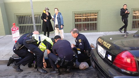 Berkeley police controlling a detainee with a spit hood on March 13, 2013. - PHOTO BY TRACIE DEANGELIS