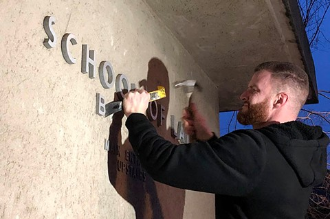 A carpenter removing Boalt Hall signage from the U.C. Berkeley law school on Thursday morning. - UC BERKELEY/ROXANNE MAKASDJIAN