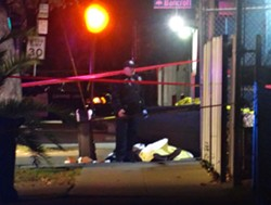 An Oakland police officer stands near the body of a man shot and killed by the police on Sunday night. - DARWIN BONDGRAHAM