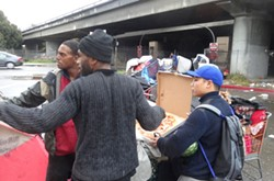Residents of the camp gather in the rain after being removed from under the 880 Freeway bridge. - DARWIN BONDGRAHAM