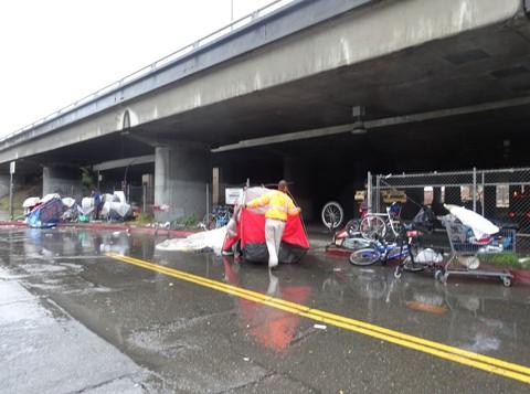 A Caltrans official drags a tent out into the rain. - DARWIN BONDGRAHAM
