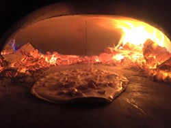 A flammekueche, or tarte flambée, in a traditional French wood-fire oven.