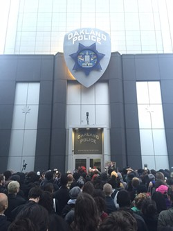 Protesters converge on Oakland police headquarters last night.