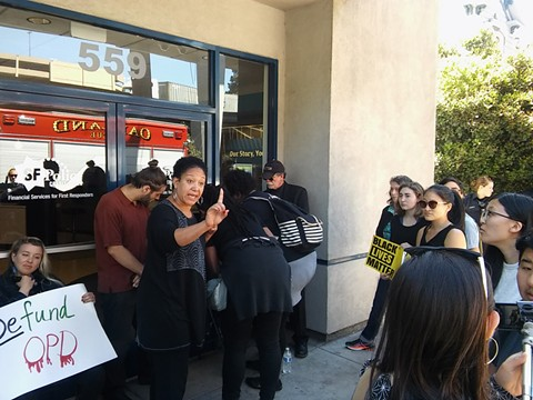 Cat Brooks of the Anti-Police Terror Project tells officers and firefighters not to attempt to remove a protester whose neck was locked to the building's door.