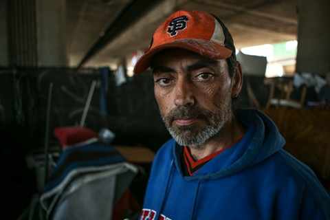 Lance Caruthers lost his laptop, tent, pictures of his children — and the only photo of his departed wife — when Caltrans conducted a sweep of the homeless camp at Brush Street near Interstate 880. - JOEL ANGEL JUAREZ