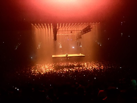 """Kanye West took a seat on his """"floating"""" stage to ramble about why he's not crazy, one of many self-aggrandizing Yeezus homilies during his Oracle Arena gig last night. - NICK MILLER"""