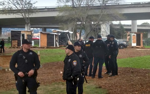"Law-enforcement officers at ""The Village"" homeless encampment this morning. The city cleared out the community, which first appeared in North Oakland in late January. - SAM LEFEBVRE"