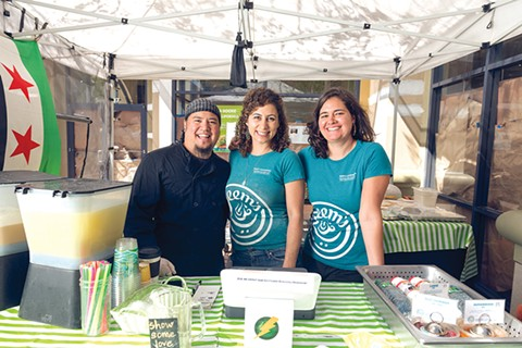 Jamal Jimenez (left) and Zaynah Hindi (right) work with Reem Assil (center) at her farmers' market stand. - LANCE YAMAMOTO