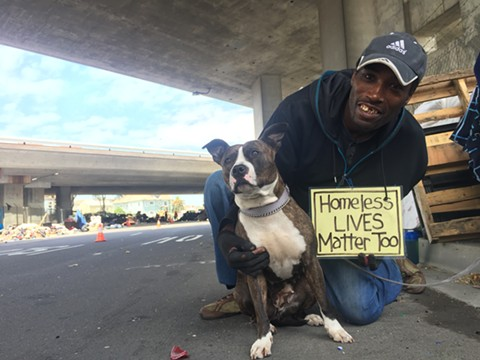 Shawn Moses at the Northgate homeless encampment on May 25, along with Princess (a pit-mix rescue that formerly lived at the San Pablo fire apartment). - PHOTO BY NICK MILLER