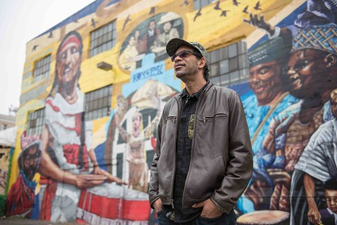 Eric Arnold standing before the Alice Street Mural. - ROSA FURNEAUX