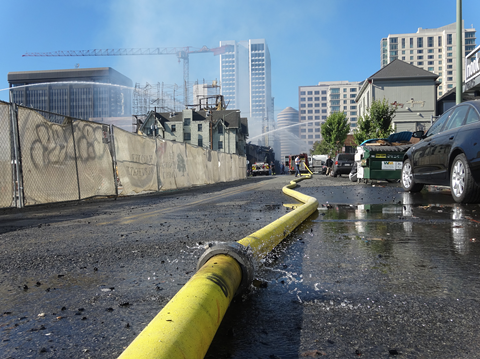 A hose runs water to the site of today's fire in Oakland's Broadway-Valdez area. - DARWIN BONDGRAHAM