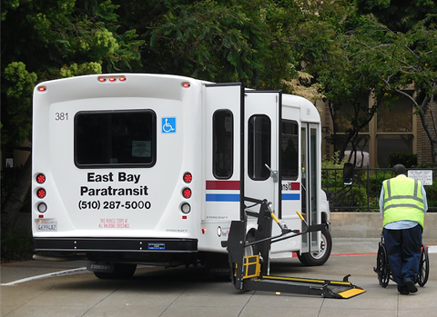 A paratransit driver helps a rider off the bus in downtown Oakland.