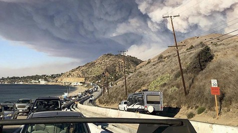"""""""The smoke plume from the fast-moving Woolsey Fire encroaching on Malibu on November 9, 2018, as residents evacuate along the Pacific Coast Highway (PCH)."""