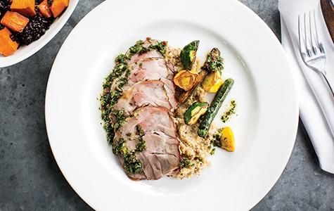 Spit-roasted pork shoulder with a side of polenta and summer squash.