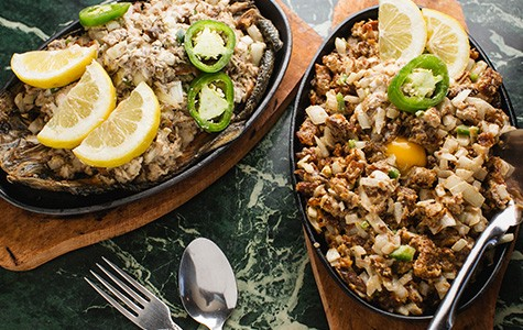 The bangus sisig (left) and pork sisig are served sizzling on hot stone plates.