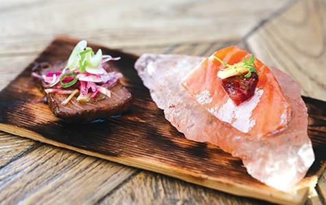 A slice of Miyazaki beef (left) and salmon sashimi on a slab of sea salt.