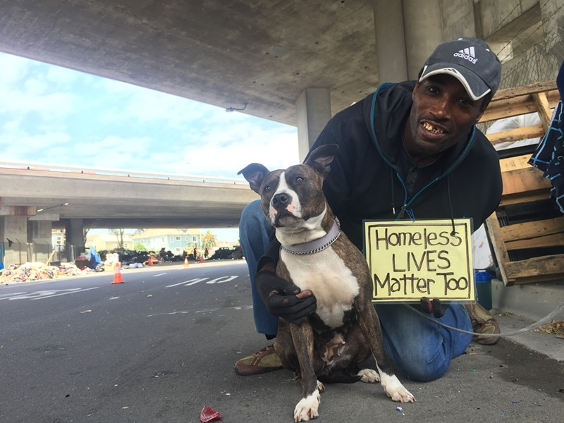 Shawn Moses at the Northgate homeless encampment last May, along with his dog Princess. - FILE PHOTO BY NICK MILLER