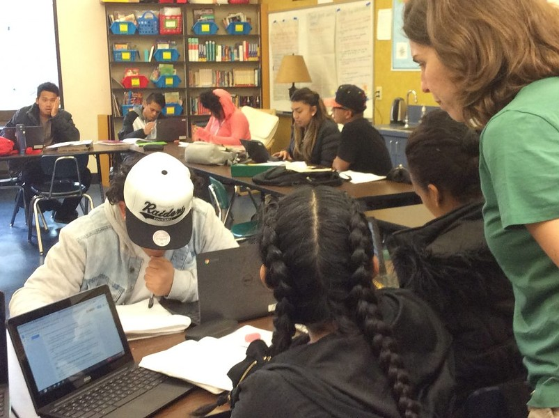 English teacher Julia Carson assists 11th-graders with writing assignments at Oakland International High. - THERESA HARRINGTON FOR EDSOURCE