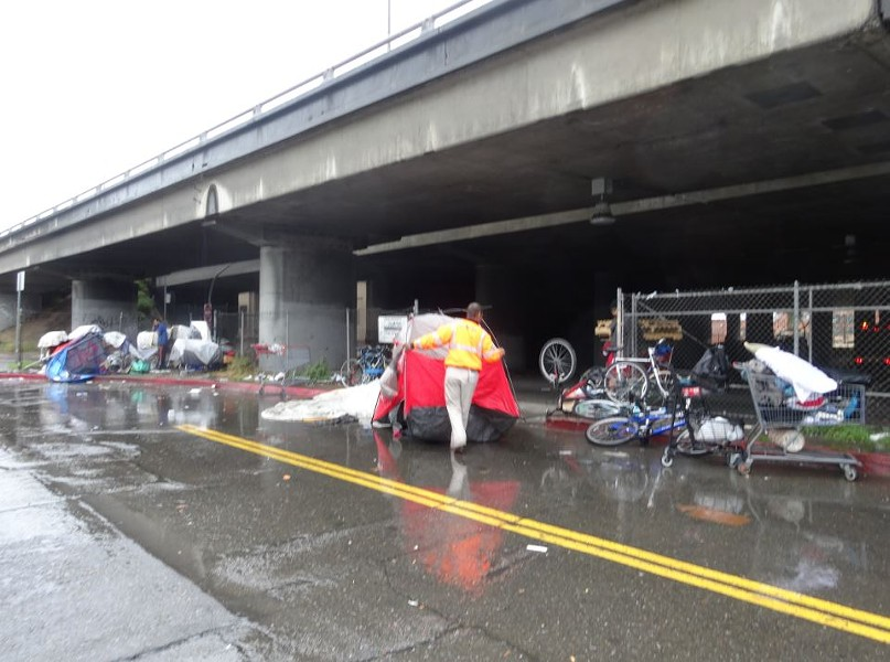A Caltrans official drags a tent out into the rain. - DARWIN BONDGRAHAM