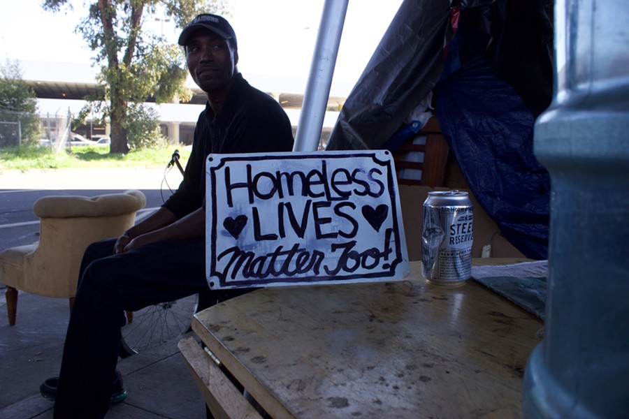 A man advocates for homeless rights at an encampment in Oakland this spring. - PHOTO BY HAYDEN BRITTON