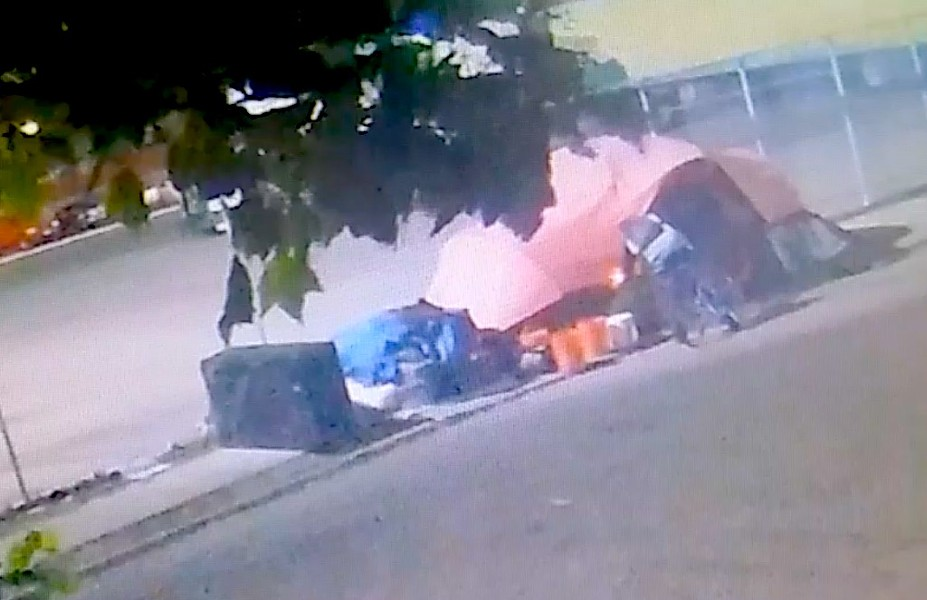 A still from surveillance video showing an unidentified man burning a tent in West Oakland last week.